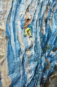 image of climbing wall  - female rock climber climbs on a rocky wall - JPG
