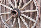 stock photo of wagon wheel  - the hub and spokes of an old wagon wheel hanging on a wall - JPG