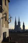 stock photo of early morning  - Silhouette of the Zagreb cathedral and many roofs seen from a plateau on Upper Town on early winter morning - JPG