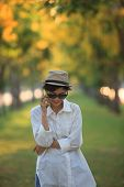 picture of people talking phone  - beautiful young woman wearing sun glassea nd straw hat talking on mobile phone with happiness emotion against blurry yellow flower in park use for people and modern life in digital connecting technology - JPG