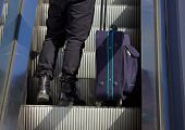 stock photo of escalator  - Low angle rear portrait of a man standing on escalator with bag - JPG