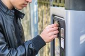 foto of dispenser  - Close up of young man paying and waiting for a parking ticket to be dispensed from the ticket booth at the side of a street