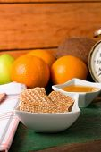 stock photo of fruit bowl  - Vertical photo of Few sesame biscuits in white bowl on green table plus next bowl with honey towel on left and fruit plus alarm clock in background  - JPG