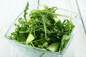 stock photo of lice  - Glass bowl of green salad on wooden table - JPG