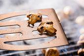 stock photo of champignons  - Champignon white mushrooms on spatula grilled on BBQ with seasoning - JPG
