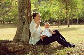 stock photo of bubbles  - Beautiful woman sitting down tree in park and leaning on trunk with her little baby on legs playing with her daughter blowing soap bubbles and smiling - JPG