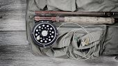 picture of vest  - Vintage concept of an antique fly fishing reel and rod with vest and flies on rustic wood - JPG