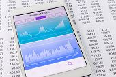 stock photo of stock market data  - Advanced chart graph and diagram with financial and stock market data application on a digital tablet pc papers with numbers on background - JPG