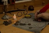 picture of treasure map  - Adventurer drawing a map in search of a lost treasure - JPG