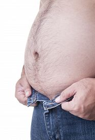 stock photo of big belly  - Chubby man with a big belly trying to wear pants - JPG