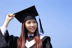 image of graduation gown  - happy graduate student girl look up to copy space and feel carefree she wear graduation cap and gown asian - JPG