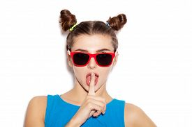 picture of hush  - Beautiful brunette woman with a finger on her lips showing to keep silence hush - JPG