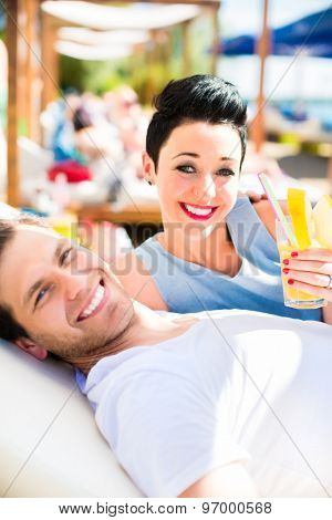 Couple in beach bar relaxing with drinks