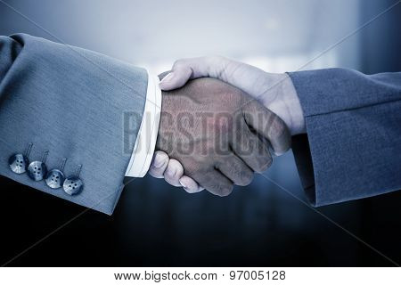 Side view of business peoples hands shaking against foyer area with elevator
