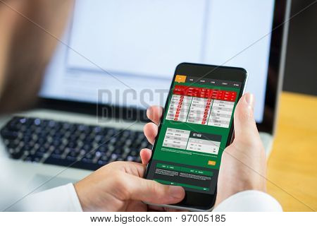 Businessman using smartphone against gambling app