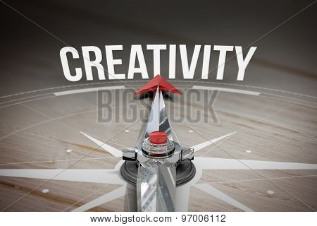 The word creativity and compass against brown wooden background