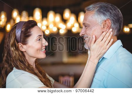 Happy woman touching her husband in the bakery store