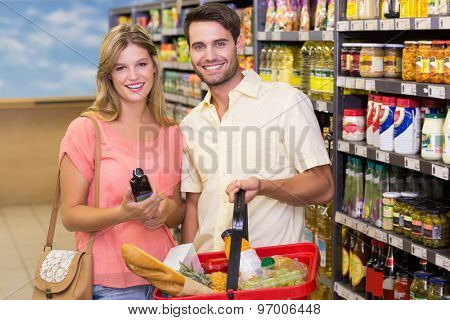 Portrait of smiling bright couple buying food products using shopping basket at supermarket