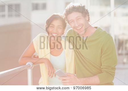 Casual couple smiling at camera outside