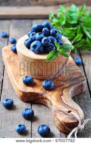 Organic fresh blueberries with peppermint on a wooden background