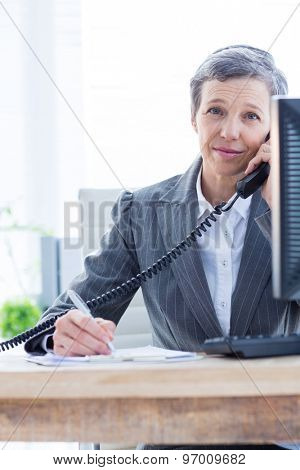 Smiling portrait of a businesswoman phoning and writing at the office