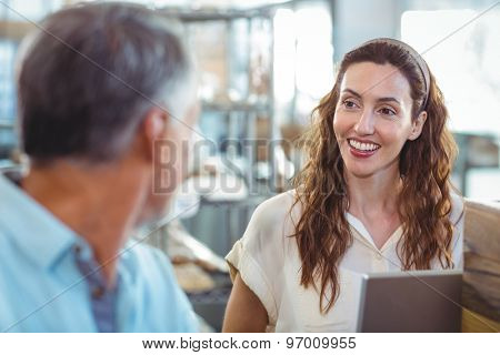 Pretty brunette smiling at her husband in the bakery store