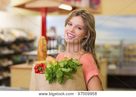 Portrait of smiling pretty blonde woman buying food products at supermarket