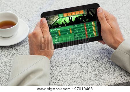 Businessman holding small tablet at table against gambling app screen