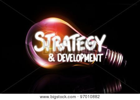 strategy and development against glowing light bulb