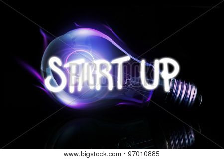 start up against glowing light bulb