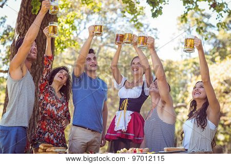 Friends toasting in the park on a sunny day