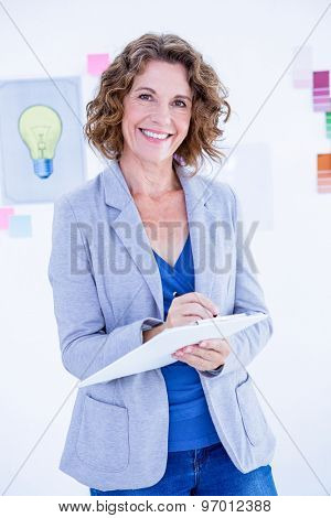 Creative businesswoman looking at camera and taking notes in office
