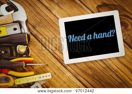 The word need a hand? and tablet pc against desk with tools