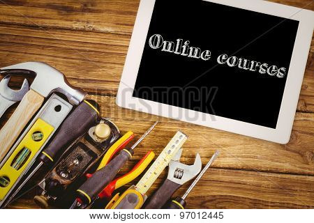 The word online courses and tablet pc against tools on desk