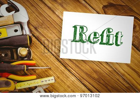The word refit and white card against desk with tools