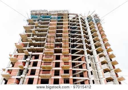 Closeup view of a tall building construction site against a white sky background