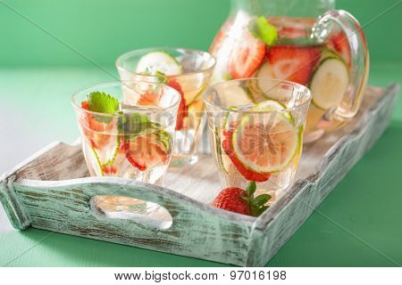refreshing summer drink with strawberry cucumber lime in jar and glasses
