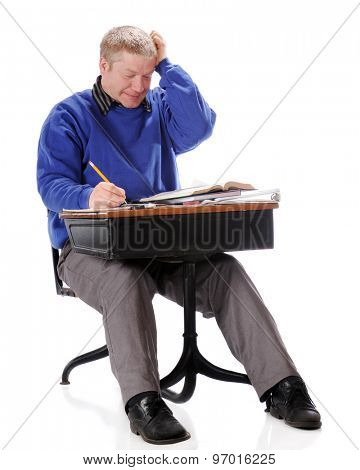 A mature man struggling with a school assignment in an old school desk.  On a white background.