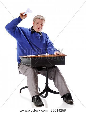 A mature student flying a paper airplane from the child's retro school desk he's sitting in.  On a white background.