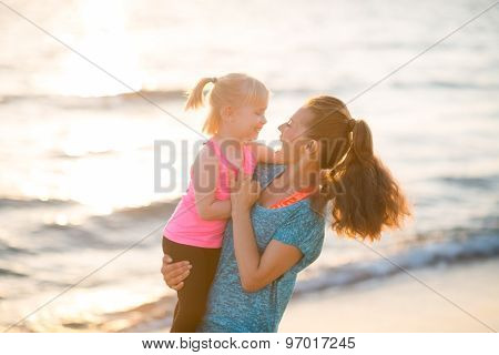 Happy Mother Holding Daughter In Her Arms By Water On Beach