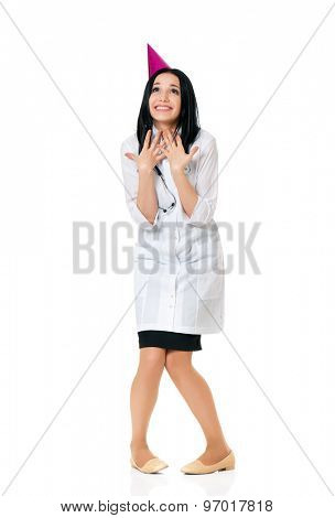 Cheerful young female doctor wearing birthday cap, isolated white background