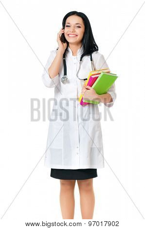 Beautiful young doctor with books holding a mobile isolated on white background