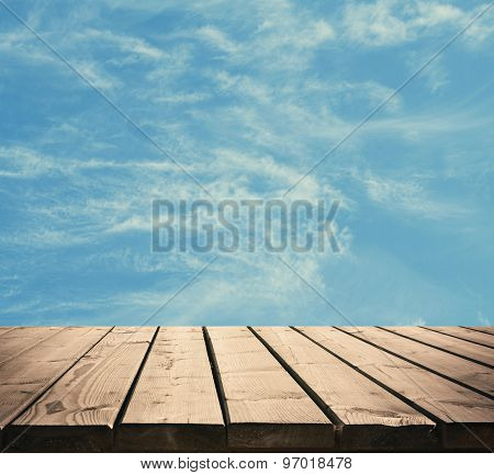 Sunny sky with clouds and wooden floor background