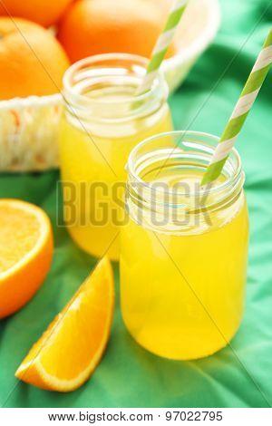 Orange Juice In Bottle And Orange In Basket On Green Background