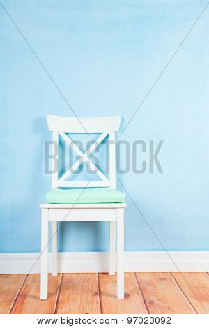 Empty chair on blue wall in interieur