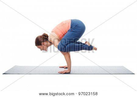 Beautiful sporty fit yogini woman practices yoga asana kakasana - crow pose isolated on white