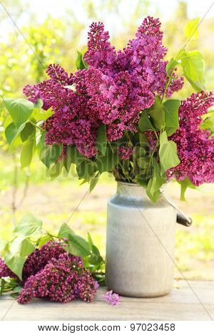 Purple Lilac Flowers In Watering Can On Wooden Background, Outdoors