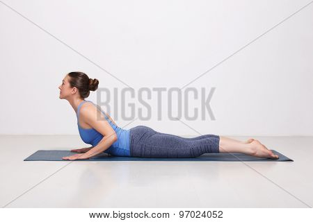 Beautiful sporty fit yogini woman practices yoga asana bhujangasana - cobra pose beginner variation in studio