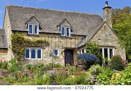 Old traditional English honey golden brown stoned cottage with colourfu flowering front garden on a