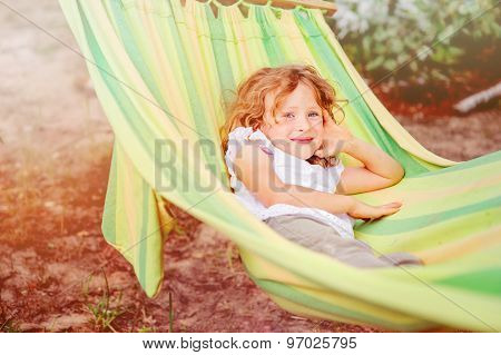 happy child girl relaxing in hammock on summer vacation